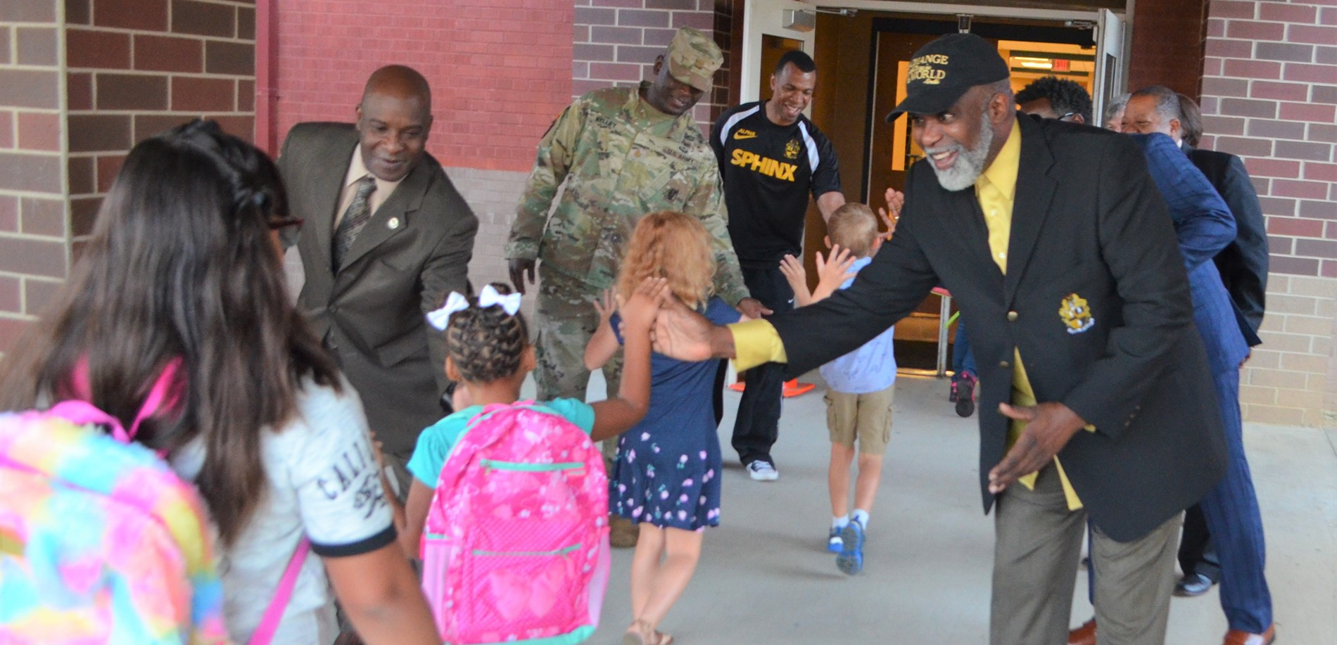 Members of the community greet students at Radcliff Elementary School.